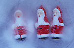 Three small models of Father Christmas in block of ice with two looking at a third with no eyes