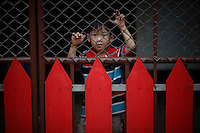 """A boy looks from behind a red fence in Sam Phrao, a village designated as """"Red Shirt Village of Democracy"""" near Udon Thani in the northeastern Thailand June 27, 2011. The red shirts, supporters of ousted premier Thaksin Shinawatra, have been branding hundreds of villages as red to rally behind Thaksin's sister, Yingluck, who is leading the opposition ahead of July 3 general elections.   REUTERS/Damir Sagolj (THAILAND)"""