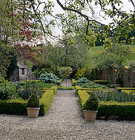A manicured garden with box hedge borders is divided by a gravel path