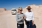 A tourist is taught the skill of divining to find an underground opal seam.   Coober Pedy, South Australia, AUSTRALIA.
