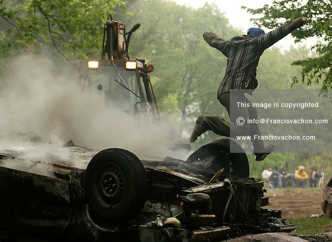 A man is jumping over a burning car during the second day of festivity of the 2006 annual Victoria Day Weekend at Trudeau Park in Tweed, Ontario