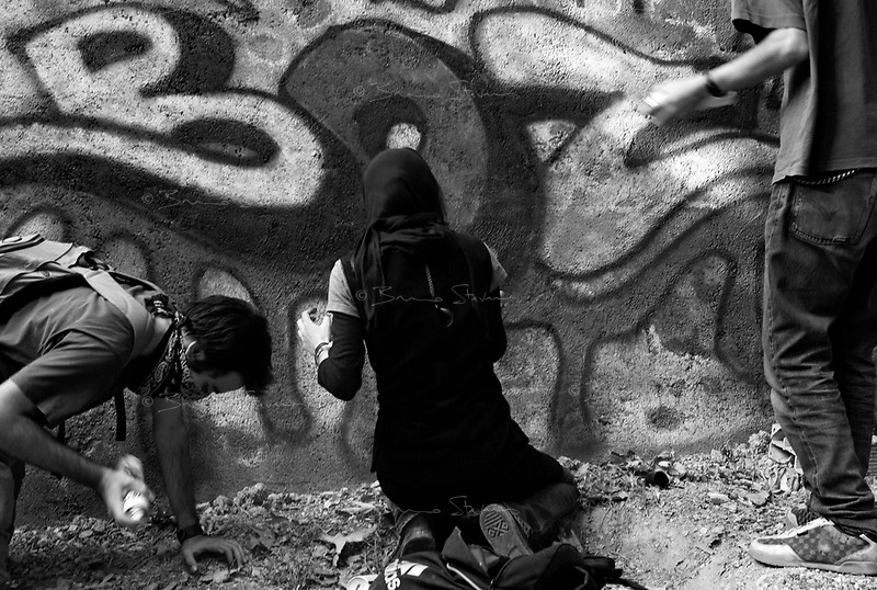 """Teheran, Iran, October 10, 2007.Young """"underground"""" artists in a northern Teheran park. Hoping for a more 'western' lifestyle, they meet up to discuss for hours in the city parks. Sometimes, some of them design 'graffs' or 'tags' on paper before trying to find a place to leave 'their' trace in the city, quite a dangerous activity in today's Iran."""