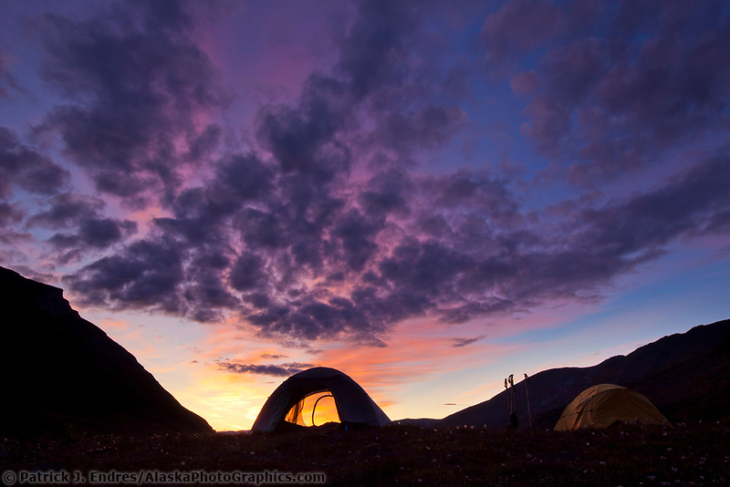 Brilliant sunrise silhouetting tent on a mountain ridge in the Arrigetch Peaks, Gates of the Arctic National Park, Alaska.
