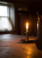 Candle in the wind: a single open window provides a light breeze to gently blow the flame on a candle in a darkened room.