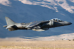 An AV-8B Harrier of the VX-9 Vampires in lowel level flight at Stead Field, Nevada. Capable of vertical take off's and landings this subsonic fighter is utilized by the Marines as a light ground attack airplane. Powered by a Rolls Royce F402-RR-408 Pegasus vectored thrust turbofan the aircraft has a maximum speed of 629 mph with a range of 685 miles,  Based in China Lake, California, The VX-9 Vampires mission includes operational evaluation of attack, fighter, and electronic warfare aircraft, weapons systems and equipment, and to develop tactical procedures for their employment. Photographed 09/06.