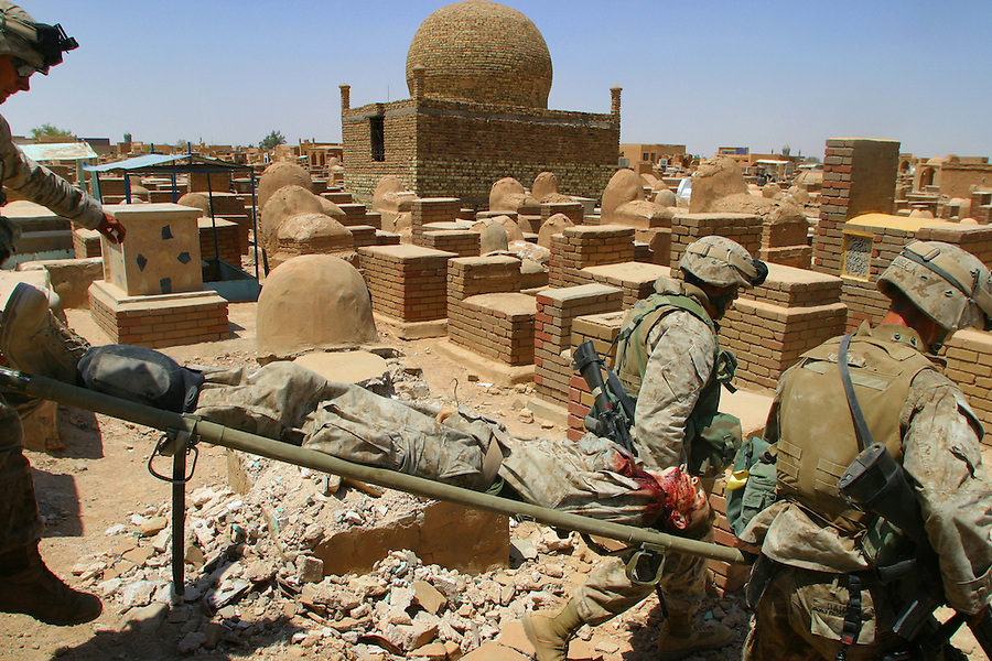 The body of a Marine - killed by a sniper's bullet - is cared for by his comrades on the second day of the battle between fighters from Moqtada al-Sadr's Mehdi Army and Marines from 1st Battalion 4th Marines and the 11th Marine Expeditionary Unit in the Valley of Peace cemetery in Najaf, Iraq on August 6, 2004.<br />