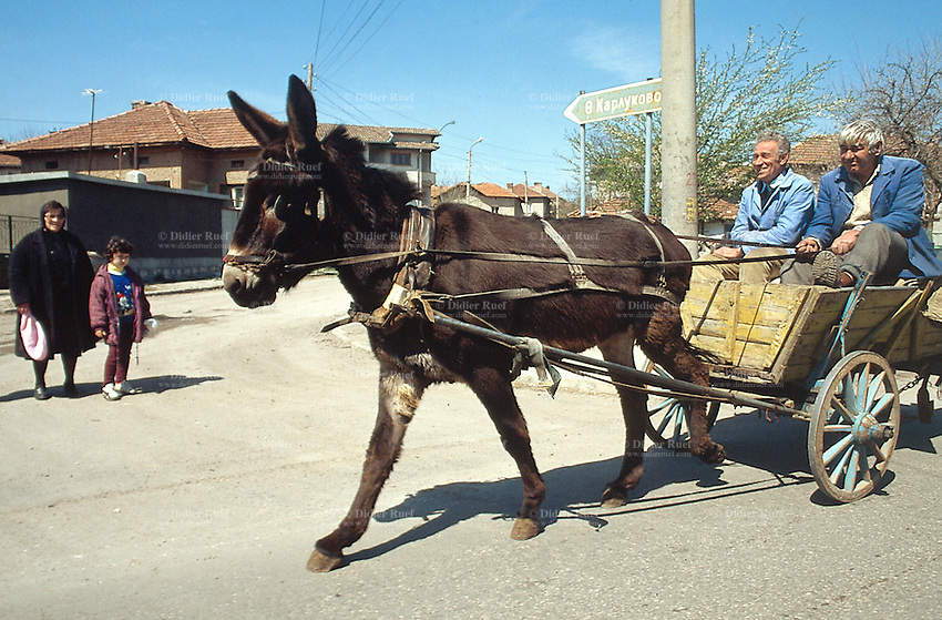 Bulgaria. Province Oblast Lovech. Lukowit. Two men seat on a cart pulled by a donkey. A mother, dressed in black, and her daughter, are on the road. © 1997 Didier Ruef