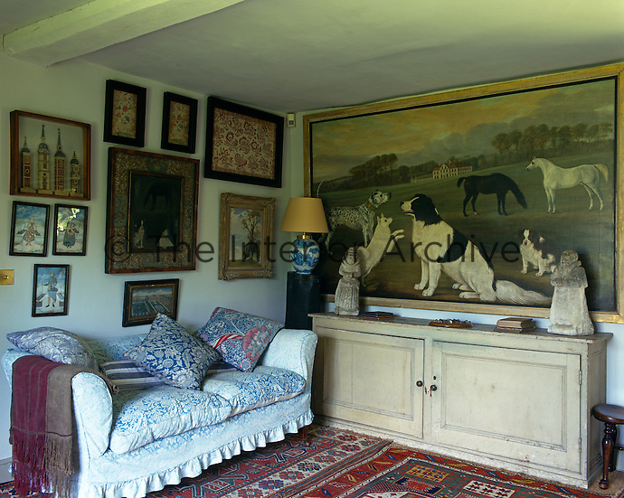 A large painting of dogs and horses above a sideboard dominates this small sitting room