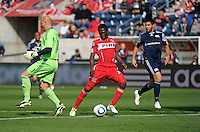 Chicago forward Patrick Nyarko (14) heads toward the New England goal after blocking an attempted clearance by New England goalkeeper Matt Reis (1).  Nyarko would score on the play.  The Chicago Fire defeated the New England Revolution 3-2 at Toyota Park in Bridgeview, IL on Sept. 25, 2011.