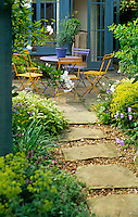 A flag-stone and gravel path leads to a paved patio and a set of painted garden chairs around a circular table