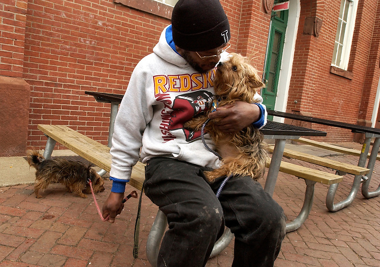 """Edward Miner takes a break at Eastern Market from his job at Market Poultry, with his Yorkshire Terriers """"Buttons,"""" right, and Buster."""