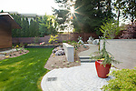 Backyard with circular stone patio, lawn, and garden beds