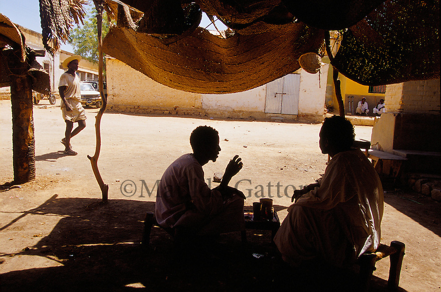 Eritrea - Keren - Men having tea in a coffee shop. As a result of 30 years of war for independence against Ethiopia (from 1961 to 1991) and another 3 years from 1997 to 2000, there are 50,000 Eritreans currently living in internally displaced (IDP) camps throughout the country. These IDPs have fled three times in the last 10 years, each time because of renewed military conflict. They lived in relatives' homes when lucky enough, but mostly, the fled to the mountains, where they attempted to do what Eritreans do best, survive. Currently there is no Ethiopian occupation in Eritrea, but landmines prevent the IDPs from finally going home. .It is estimated that every Eritrean family lost two or three members to the war which makes the reality of the current emergency situation even more painful for Eritreans worldwide. Currently, the male population has been decreased dramatically, affecting the most fundamental socio-economic systems in the country. Among the refugee population, an overwhelming majority of families are female-headed, severely affecting agricultural production. For, IDPs in particular, 80% of households are female-headed..The unresolved border dispute with Ethiopia remains the most important drawback to Eritrea's socio-economic development, as national resources (human and material) continue to be prioritized for national defense. Eritrea is vulnerable to recurrent droughts and variable weather conditions with potentially negative effects on the 80 percent of the population that depend on agriculture and pastoralism as main sources of livelihood. The situation has been exacerbated by the unresolved border dispute, resulting in economic stagnation, lack of food security and increased susceptibility of the population to various ailments including communicable diseases and malnutrition..