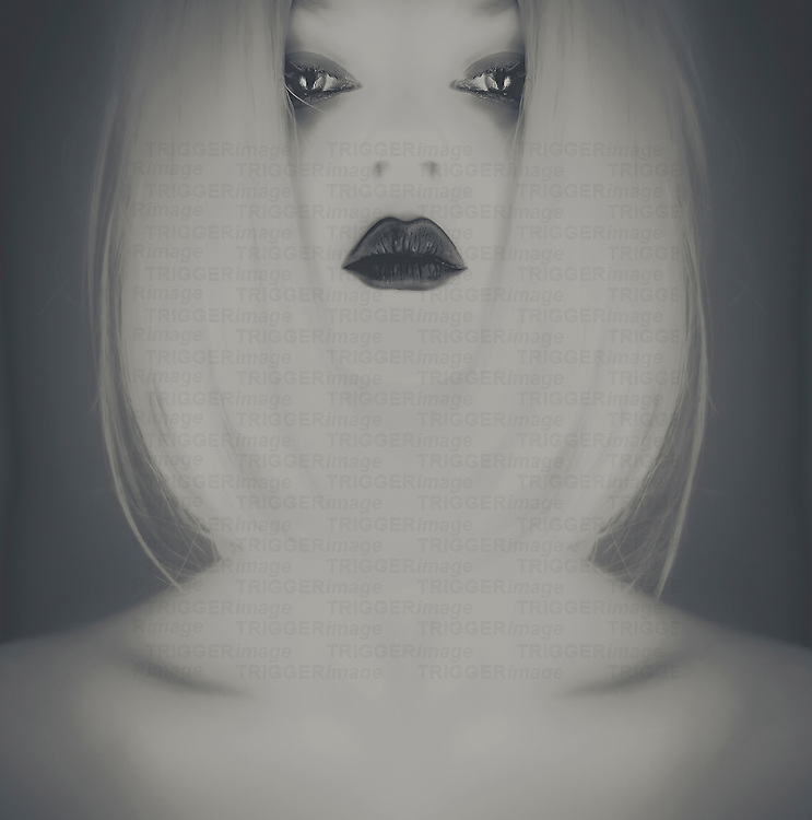 Conceptual image of a young adult woman's face with white hair looking at camera