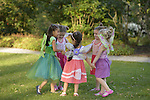 Five girls, JULIA DELGADO in peach dress; 4 1/2 year old triplets: ARIELLE KIRCHHOFER in orange dress, CRISTINA KIRCHHOFER in pink dress, BRIANNA KIRCHHOFER in purple dress; and PRISCILA BLANCHET, 4 years old, in green fairy costume, are best friends from Bayside, Queens, who have come with their families to see the Lori Belilove & The Isadora Duncan Dance Company dance throughout the gardens during the Midsummer Night event at the Long Island Gold Coast estate of Old Westbury Gardens on the first day of summer, the summer solstice.