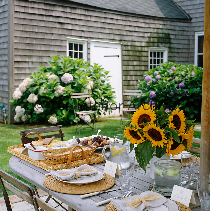 The garden table is laid for lunch and decorated with a vase of fresh sunflowers