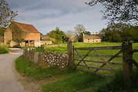 Traditional old stone barn and stone slab fencing in Kelmscott, The Cotswolds, Gloucestershire, UK