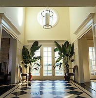 Large tropical houseplants make a dramatic statement in the entrance hall of a house in East Hampton
