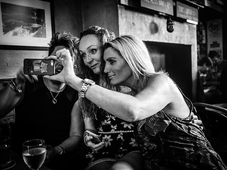 Three people taking a selfie photograph on a mobile phone