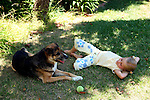 Young girl and her dog take a break and rest in shade on a sunny day.