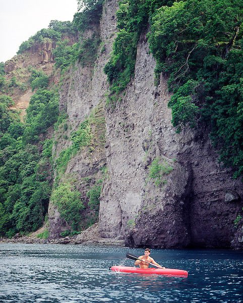 SOUFRIERE, DOMINICA : A adventure tourist enjoys kayaking in Dominica's  Scotts Head Marine Reserve. An immense bay, the Scotts Head Marine Reserve is formed in the south by the Scotts Head peninsula and extends north some two miles to the coastal area of Anse Bateaux, providing a cove-like setting for the fishing villages of Soufriere and Lydiaville. Kayaker's are usually looking for dolphins and Pilot whales. Soufriere, Dominica , Eastern Caribbean.