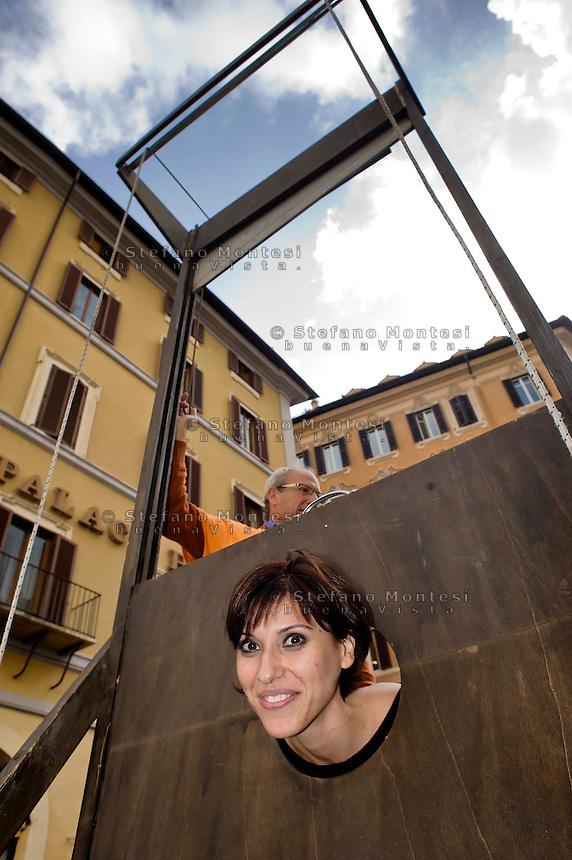 Roma 5 Novembre 2014<br /> Manifestazione davanti al Parlamento, dell'associazione, &quot;Tutti a scuola&quot;, per protestare contro  legge di stabilit&agrave; del Governo Renzi, che taglia i  fondo nazionale della non autosufficienza e   cancella i diritti dei disabili. I manifestanti  portano una ghigliottina per decapitare simbolicamente i politici. La deputata Maria Marzana del Movimento Cinque Stelle si sottopone alla ghigliottina<br /> Rome November 5, 2014 <br /> Demonstration in front of the Parliament of the association &quot;Everybody to School&quot; to protest against the law of stability of the  Prime Minister Renzi's government, which cuts the bottom of national self-sufficiency and cancels out the rights of the disabled. Protesters carry a guillotine to decapitate symbolically politicians. Maria Marzana deputy Five Star Movement is subjected to the guillotine.
