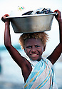 Linette, a young girl from Tembin village on the West Coast of New Ireland carries laundry to the river..Tembin, New Ireland Province, Papua New Guinea