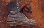 Well-worn black heavy-duty industrial working boot lying on rusty metal sheet