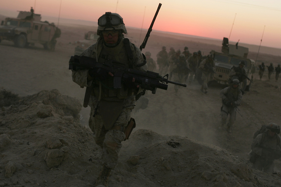 Marines from Golf Co. 2nd Battalion 1st Marines and Iraqi soldiers rush from their attack positions in a pre-dawn sweep into the Iraqi-Syrian border town of Ubaydi as part of Operation Steel Curtain on Tues. Nov. 14, 2005.