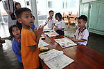 "Children look up from their coloring books as members of Veterans for Peace pay a visit to the Duc Son Pagoda orphanage in Hue, Vietnam. The group toured Vietnam in April to learn about efforts to mitigate the suffering of the country's Agent Orange victims and  others who have been injured or killed by bombs and land mines left over from the Vietnam War.  The facility is currently home to 170 children. Relying solely on donations, the nuns who run the orphanage have sent 140 children to university or vocational school since they opened its doors in 1987. ""Only love can make the world warmer and more peaceful,"" its director says. April 22, 2013."
