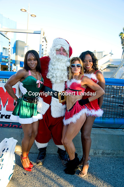 Women body builders pose with Santa Claus at Muscle Beach in Venice, CA