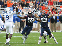 Duke quarterback Thaddeus Lewis (9) gets pressure from Virginia defensive tackle John-Kevin Dolce (59) and Virginia linebacker Steve Greer (53) during an ACC football game Saturday in Charlottesville, VA. Duke won 28-17. Photo/Andrew Shurtleff