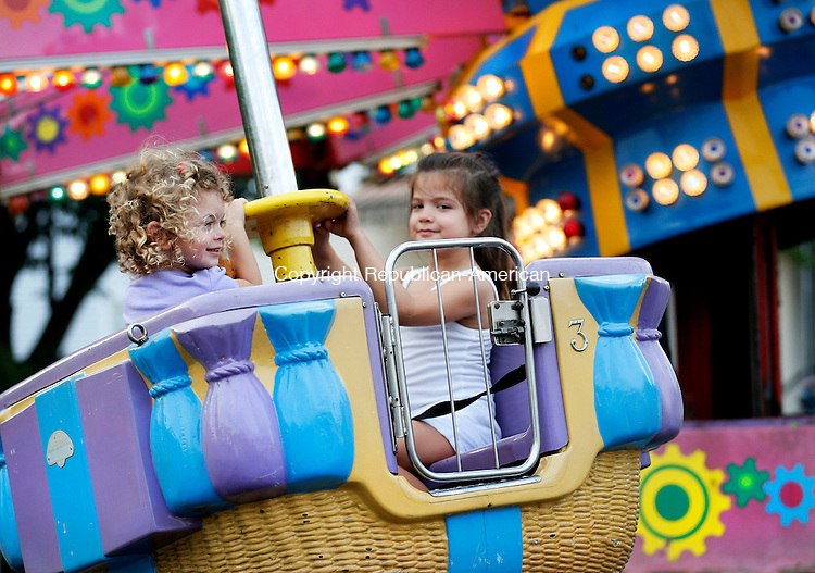 Beacon Falls, CT- 11 June 2015-061115CM07-  Heidi Lamb 3, of Prospect, left, and Ella Iannone 5, of Prospect ride the Zamperla during the annual Beacon Hose Carnival in Beacon Falls on Thursday.  The rides, food and entertainment continue Friday from 6 p.m. to 11p.m. then on Saturday from 3 p.m. to midnight with a parade at 6 p.m.  The event is put on by Beacon Hose Co. 1.      Christopher Massa Republican-American