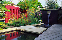 View across reflective pool showing water feature and vermillion and aubergine rendered wall