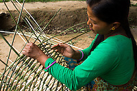 Kalpana Tamang (40), weaves a bamboo basket in front of her temporary shelter in Kavre, Bagmati, Nepal on 30 June 2015.  Kalpana, a widow with 3 children, has been supported by SOS Children's Villages for many years now and had receive the Home-in-a-Box after the earthquake destroyed her house, almost killing her two daughters. She now lives in a temporary shelter, sharing her dwelling with farm animals, and is trying to make ends meet by weaving bamboo baskets to supplement the financial assistance provided by SOS Childrens Villages. The NGO mostly supports her children's welfare and schooling as well as provides her with essential household and schooling items like kitchen utensils and school books and uniforms. Photo by Suzanne Lee for SOS Children's Villages