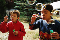 Girl and boy (7-9) blowing bubble-wands, outdoors (Licence this image exclusively with Getty: http://www.gettyimages.com/detail/200387446-001 )