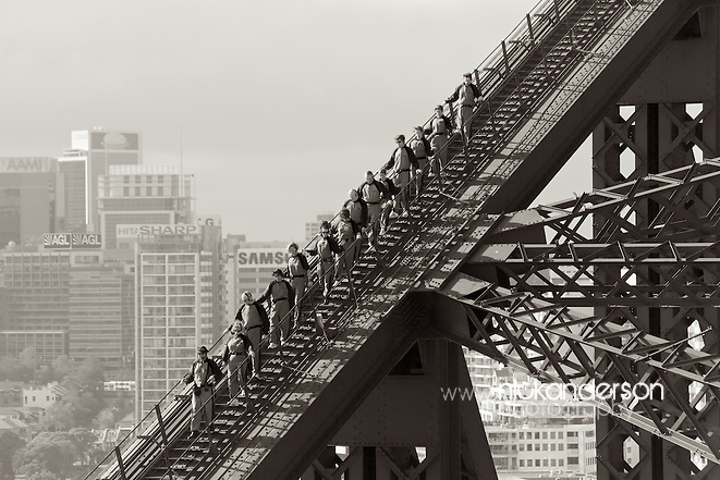 Walkers carefully making their way down the southern end of the huge arch of Sydney Harbour Bridge, with highrises of North Sydney in the background.  All the BridgeClimb participants are securely harnessed & are being led by an experienced guide (Nick Anderson)