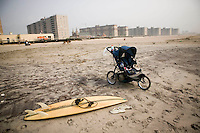 A stroller and surfboard wait on the sand at Far Rockaway beach in New York, United States, 17 September 2005. Photo Credit: David Brabyn.