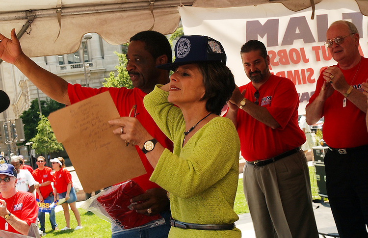 Sen. Barbara Boxer, D-Calif., dons a new hat given to her by Robert Roach Jr., left, IAM General Vice President of Transportation, after she spoke at a rally of the International Association of Machinists and Aerospace Workers (IAM), in which they encourge participation in the presidential election protested anti-worker polices of the Bush Administration.  The rally was held in Freedom Plaza after they marched from Capitol Hill.