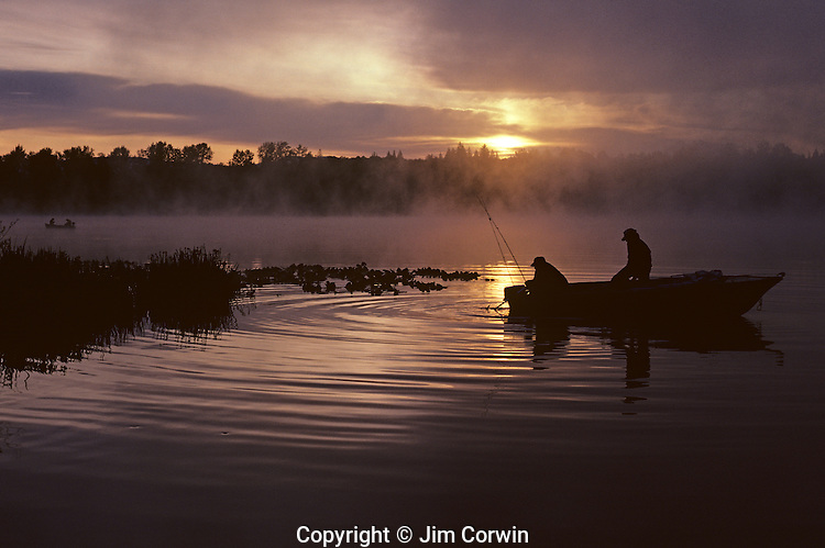 Sunrise at Lake Cassidy in fog with silhouetted fisherman in small rowboat getting ready to fish, east of Marysville, Washington State USA.