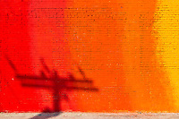 Late afternoon sun projects long shadows of utility pole on a colorful red/orange wall mural.
