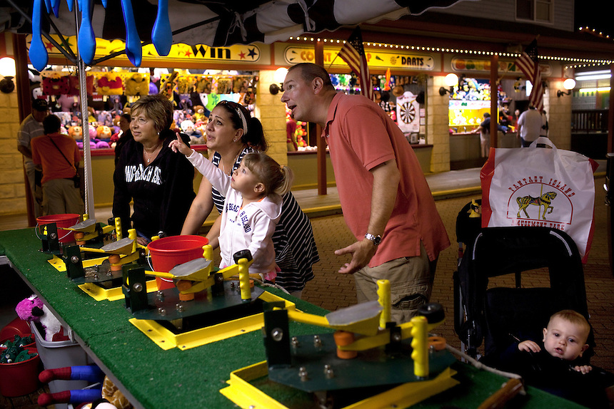 Long Beach Island, NJ - June 29, 2013 :  Skylar Whitley, 3, center, from Sparta, NJ, points out a toy to her family Janice Morgan, Dawn Whitley, John Whitley and little brother Nolan Whitley, 11mths, at Fantasy Island Amusement Park in Beach Haven on Long Beach Island, NJ on June 29, 2013. People are returning to the beaches for the summer after recovery efforts post Superstorm Sandy.