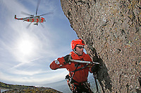 Rescue paramedic Lars Markengbakken working on a bolt that is being used to secure him to the rock face. <br />