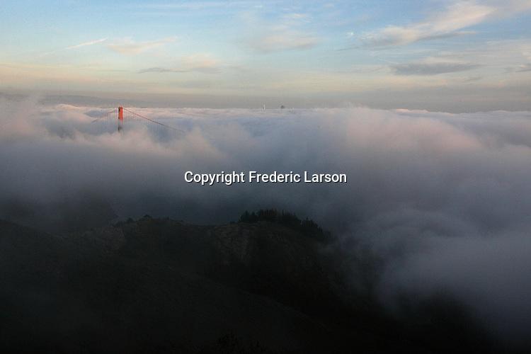 The fog roll under the Golden Gate Bridge engulfing the  San Francisco Bay.