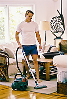Man in boxer underwear vacuuming living room rug