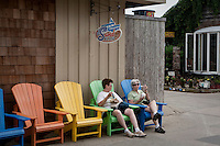 Two women sit on coloured chairs in Ocean Beach on Fire Island in New York state, Wednesday August 3, 2011. The incorporated villages of Ocean Beach and Saltaire within Fire Island National Seashore are car-free during the summer tourist season and permit only pedestrian and bicycle traffic.