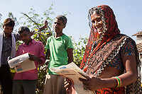 Kamlesh Kumari (right), 28, receives this week's Khabar Lahariya newspaper from Sunita (unseen) at her house in a village in Chitrakoot, Uttar Pradesh, India on 5th December 2012. Kamlesh, a mother of 2, is a farmer, earning about 20000 rupees of sales per annum from her 2 acre farm. She dreams of becoming a journalist for Khabar Lahariya but is not able to apply since the newspaper only takes one reporter in each area, and Sunita is already working in the area. Kamlesh reads the papers out loud to her whole family and illiterate friends. Photo by Suzanne Lee for Marie Claire France.