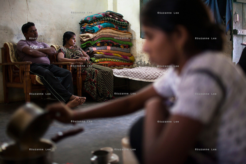Sharda Solanki (center), 36, sits with her husband Kantibhai (left), 38, as their daughter Rasmi, 20, makes tea in a house, built using the money Sharda made from her surrogacies, in Anand, Gujarat, India on 9th December 2012. While Kantibhai works as a security guard earning 5000 rupees per month, Sharda had made hundreds of thousands with 2 surrogacies that she did with Akanksha Clinic, which she used to buy land, buffaloes, build washrooms in her house and extend the house. She had also saved a substantial amount to fund her 3 children's educations and make sure that her 2 daughters will find husbands to match their current status. Photo by Suzanne Lee / Marie-Claire France