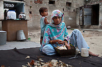 Nafeesa, 27, rolls bidis (indian cigarettes) as her the youngest of her 4 children (aged 10, 7, 4, and 1 and a half years), play in her house compound in a slum in Tonk, Rajasthan, India, on 19th June 2012. Nafeesa's health deteriorated from bad birth spacing and over-working. While her husband works far from home, she rolls bidis to make an income and support the family. She single-handedly runs the household and this has taken a toll on her health and financial insufficiencies has affected her children's health. Photo by Suzanne Lee for Save The Children UK