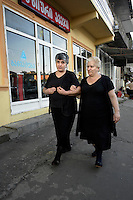 Women dressed in black walk through Batumi.